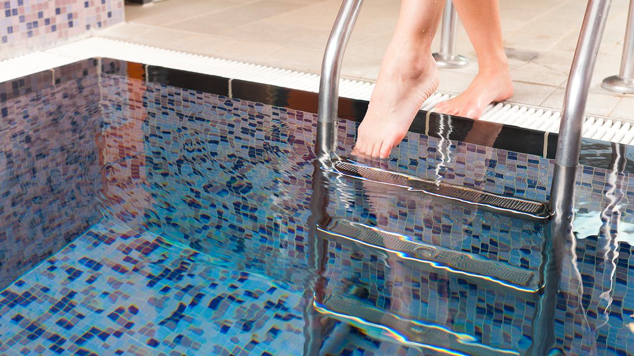 Junge Frau steigt in ein Wasserbecken
