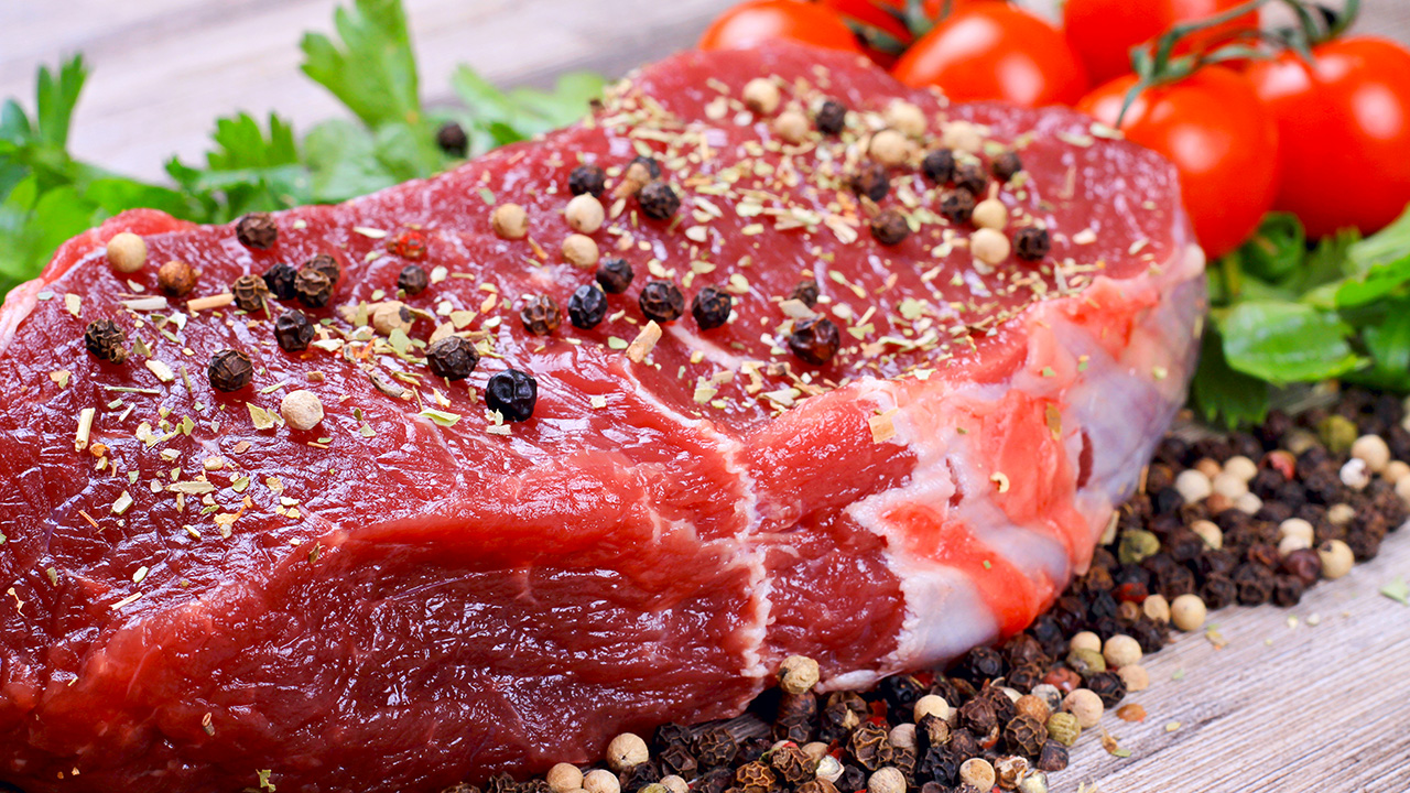 Raw beefsteak with spices and cherry tomatoes on wooden background